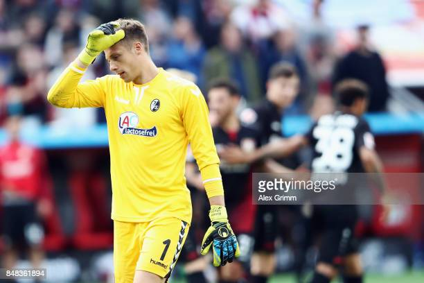 Goalkeeper Alexander Schwolow of Freiburg reacts as Kevin Volland of Leverkusen celebrates his team's third goal with team mates during the...