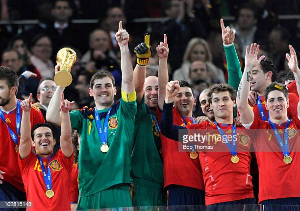 Goalkeeper and captain Iker Casillas of Spain lifts the trophy and celebrates with teammates after the 2010 FIFA World Cup Final between the...