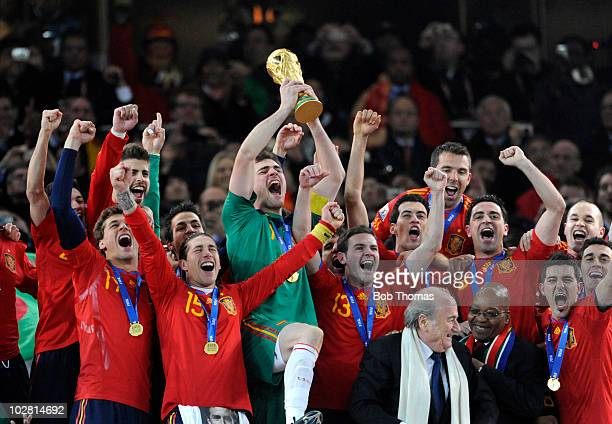 Goalkeeper and captain Iker Casillas of Spain lifts the World Cup and celebrates with teammates after the 2010 FIFA World Cup Final between the...