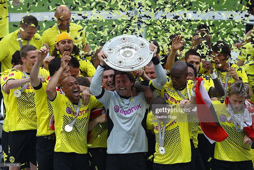 Goalkeeper and captain <a gi-track='captionPersonalityLinkClicked' href=/galleries/search?phrase=Roman+Weidenfeller&family=editorial&specificpeople=726753 ng-click='$event.stopPropagation()'>Roman Weidenfeller</a> of Dortmund rises the trophy and celebrates with team mates winning the German Championship after the Bundesliga match between Borussia Dortmund and Eintracht Frankfurt at Signal Iduna Park on May 14, 2011 in Dortmund, Germany.