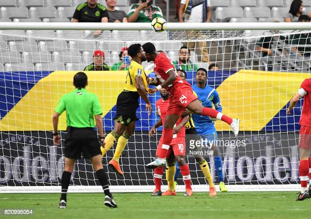 Goalkeeper Andre Blake of Jamaica gets ready to make a save as teammate Jermaine Taylor challenges the header by Cyle Larin of Canada in a...