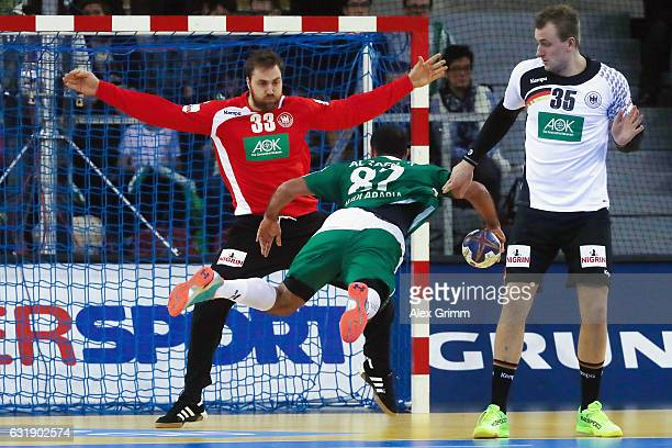 Goalkeeper Andreas Wolff of Germany is challenged by Mohammed Alzaer of Saudi Arabia during the 25th IHF Men's World Championship 2017 match between...