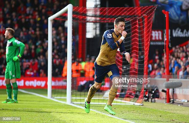 Goalkeeper Artur Boruc of Bournemouth looks dejected as Mesut Oezil of Arsenal celebrates as he scores their first goal during the Barclays Premier...