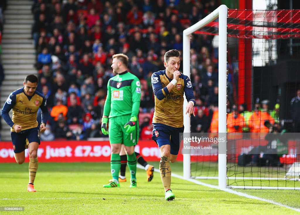 Goalkeeper <a gi-track='captionPersonalityLinkClicked' href=/galleries/search?phrase=Artur+Boruc&family=editorial&specificpeople=554761 ng-click='$event.stopPropagation()'>Artur Boruc</a> of Bournemouth looks dejected as Mesut Ozil of Arsenal celebrates as he scores their first goal during the Barclays Premier League match between A.F.C. Bournemouth and Arsenal at the Vitality Stadium on February 7, 2016 in Bournemouth, England.