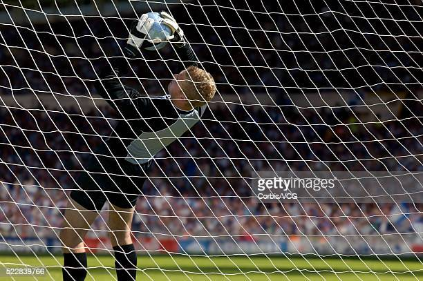 Goalkeeper attempting to prevent the ball entering the net at soccer match