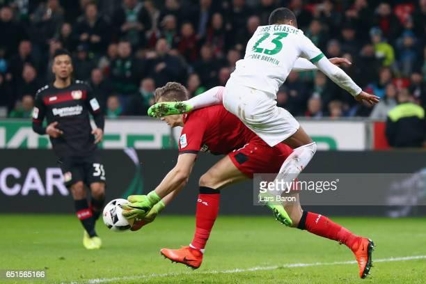 Goalkeeper Bernd Leno of Leverkusen is hit by Theodor Gebre Selassie of Bremen during the Bundesliga match between Bayer 04 Leverkusen and Werder...