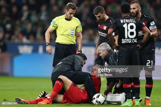 Goalkeeper Bernd Leno of Leverkusen receives treatment after being hit by Theodor Gebre Selassie of Bremen during the Bundesliga match between Bayer...
