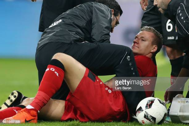 Goalkeeper Bernd Leno of Leverkusen receives treatment after being hit by Theodor Gebre Selassie of Bremen during the Bundesliga match between Bayer...