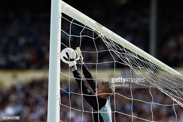 Goalkeeper blocking ball at soccer match