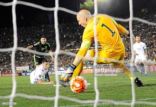 Goalkeeper Brad Guzan of the United States unable to stop a goal by Oribe Peralta of Mexico as teammate Geoff Cameron and Fabian Johnson of the...