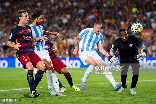 Goalkeeper Carlos Kameni of Malaga CF blocks the ball next to his teammates Raul Albentosa and Marcos Angeleri and Ivan Rakitic of FC Barcelona...