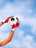 Goalkeeper catching football against sky, close-up of arms and hands