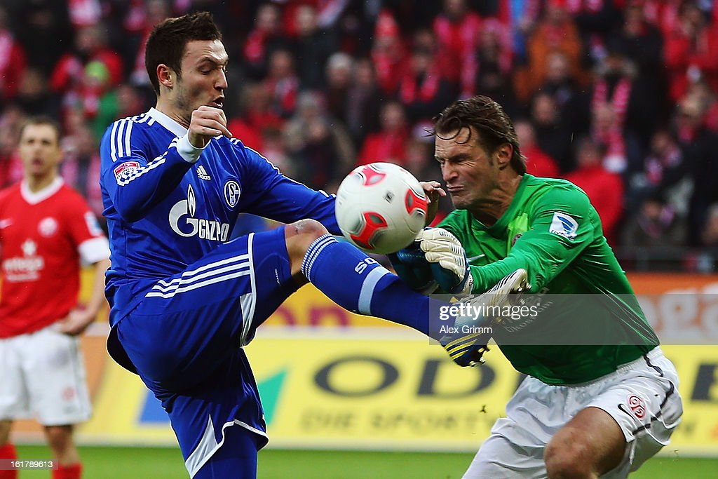 Goalkeeper Christian Wetklo of Mainz is challenged by <a gi-track='captionPersonalityLinkClicked' href=/galleries/search?phrase=Marco+Hoeger&family=editorial&specificpeople=6872414 ng-click='$event.stopPropagation()'>Marco Hoeger</a> of Schalke during the Bundesliga match between 1. FSV Mainz 05 and FC Schalke 04 at Coface Arena on February 16, 2013 in Mainz, Germany.