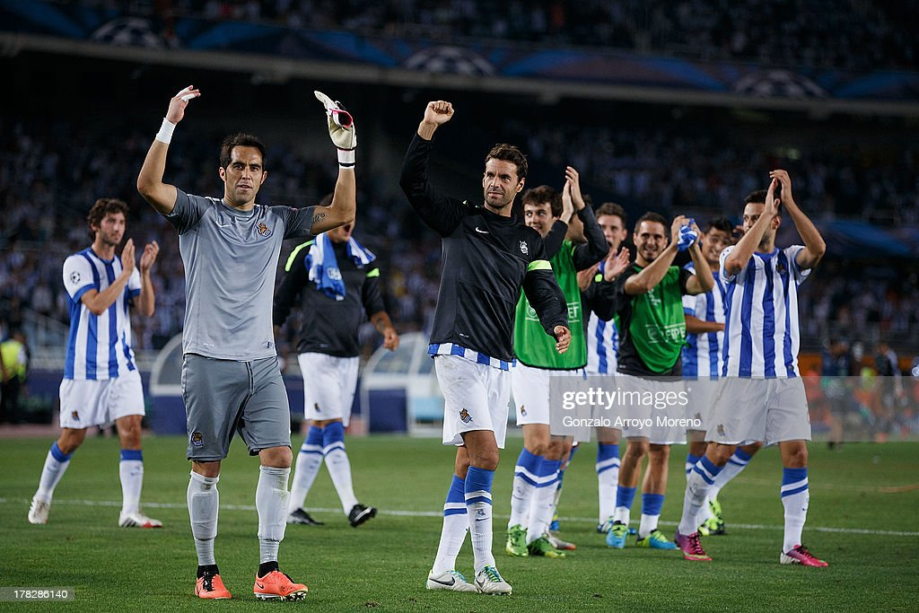 Goalkeeper <a gi-track='captionPersonalityLinkClicked' href=/galleries/search?phrase=Claudio+Bravo&family=editorial&specificpeople=2715784 ng-click='$event.stopPropagation()'>Claudio Bravo</a> (2nd L) of Real Sociedad and teammate Enaut Zubikarai (3rd L) acknowledge the fans after the UEFA Champions League Play-offs second leg match between Real Sociedad and Olympique Lyonnais at Estadio Anoeta on August 28, 2013 in San Sebastian, Spain.