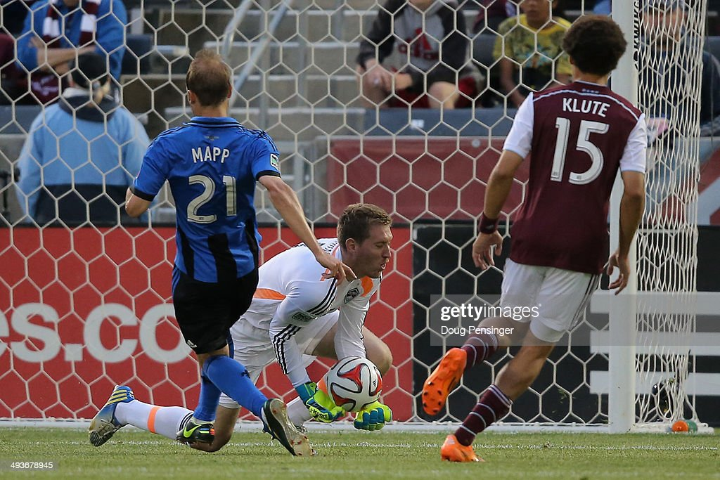 Goalkeeper Clint Irwin of the Colorado Rapids collects the ball against Justin Mapp of the Montreal Impact as Chris Klute of the Colorado Rapids...