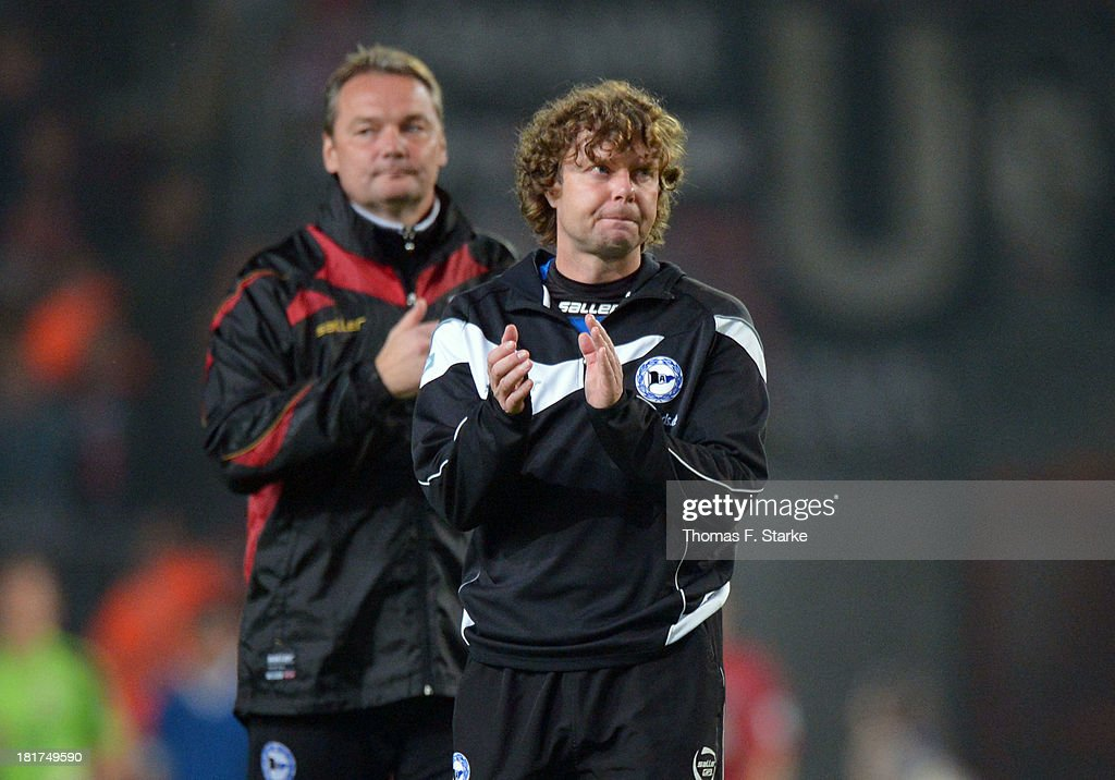 Goalkeeper coach Marco Kostmann (L) and head coach Stefan Kraemer of Bielefeld applaud after the DFB Cup match between Arminia Bielefeld and Bayer 04 Leverkusen at Schueco Arena on September 24, 2013 in Bielefeld, Germany.