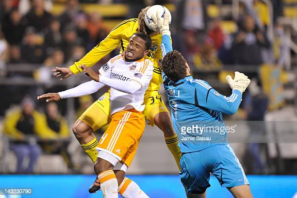 Goalkeeper Colin Clark of the Houston Dynamo makes the save as Aaron Schoenfeld of the Columbus Crew attempts to head the ball past Clark and...