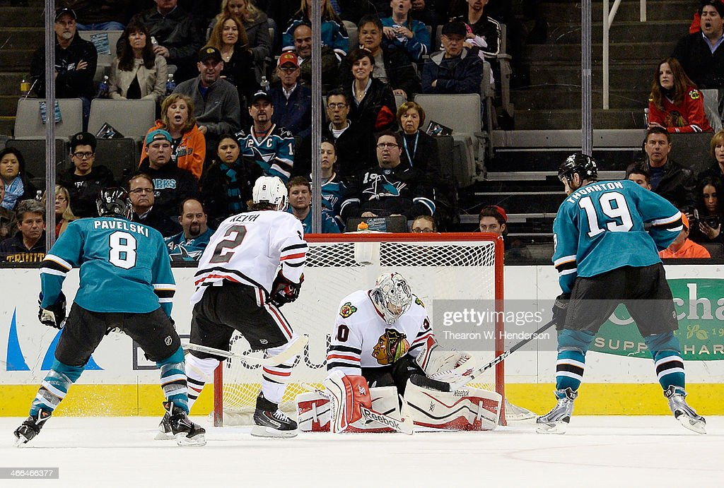 Goalkeeper Corey Crawford #50 of the Chicago Blackhawks blocks the shot of Joe Thornton #19 of the San Jose Sharks during the first period at SAP Center on February 1, 2014 in San Jose, California.