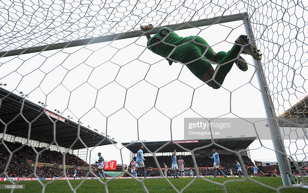 Goalkeeper Costel Pantilimon of Man City hangs from the crossbar after a shot goes over during the FA Cup Fourth Round match between Stoke City and Manchester City at Britannia Stadium on January 26, 2013 in Stoke on Trent, England.