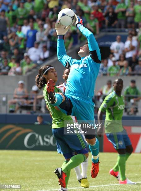 Goalkeeper Dan Kennedy of Chivas USA blocks a shot by Zach Scott of the Seattle Sounders FC at CenturyLink Field on September 8 2012 in Seattle...