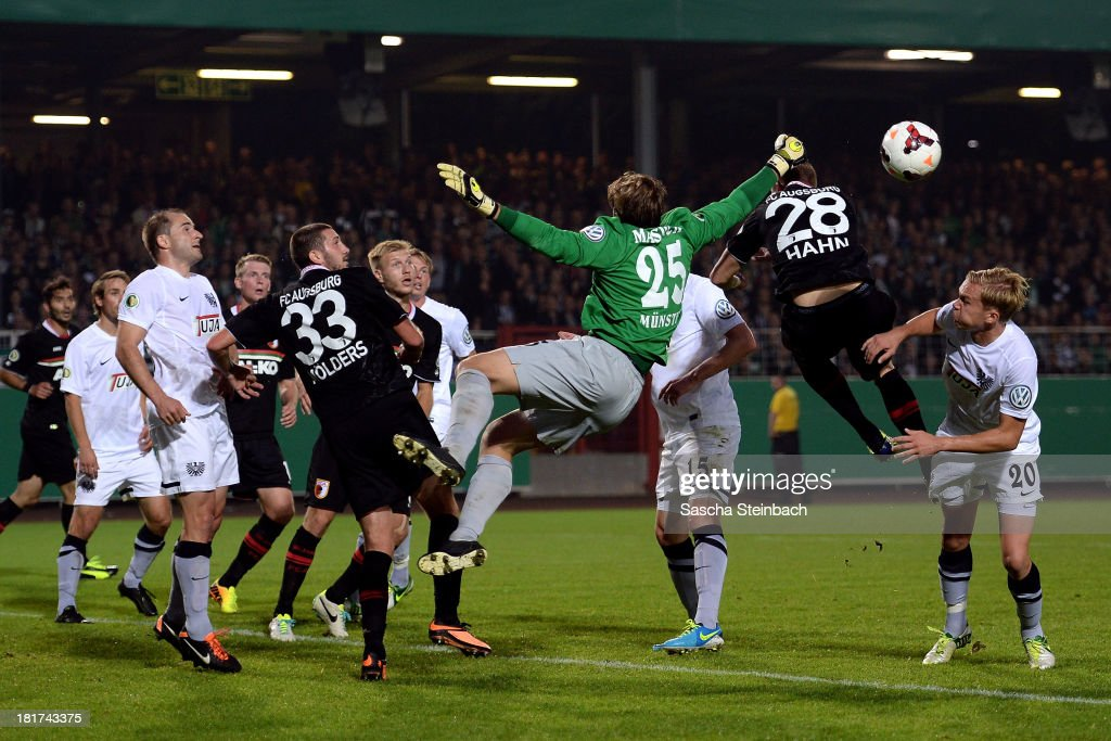Goalkeeper Daniel Masuch of Preussen Muenster punches the ball clear from a corner despite a challenge by <a gi-track='captionPersonalityLinkClicked' href=/galleries/search?phrase=Sascha+Moelders&family=editorial&specificpeople=4296304 ng-click='$event.stopPropagation()'>Sascha Moelders</a> and Andre Hahm (R) during DFB Cup second round match between Preussen Muenster and FC Augsburg at Preussenstadion on September 24, 2013 in Muenster, Germany.
