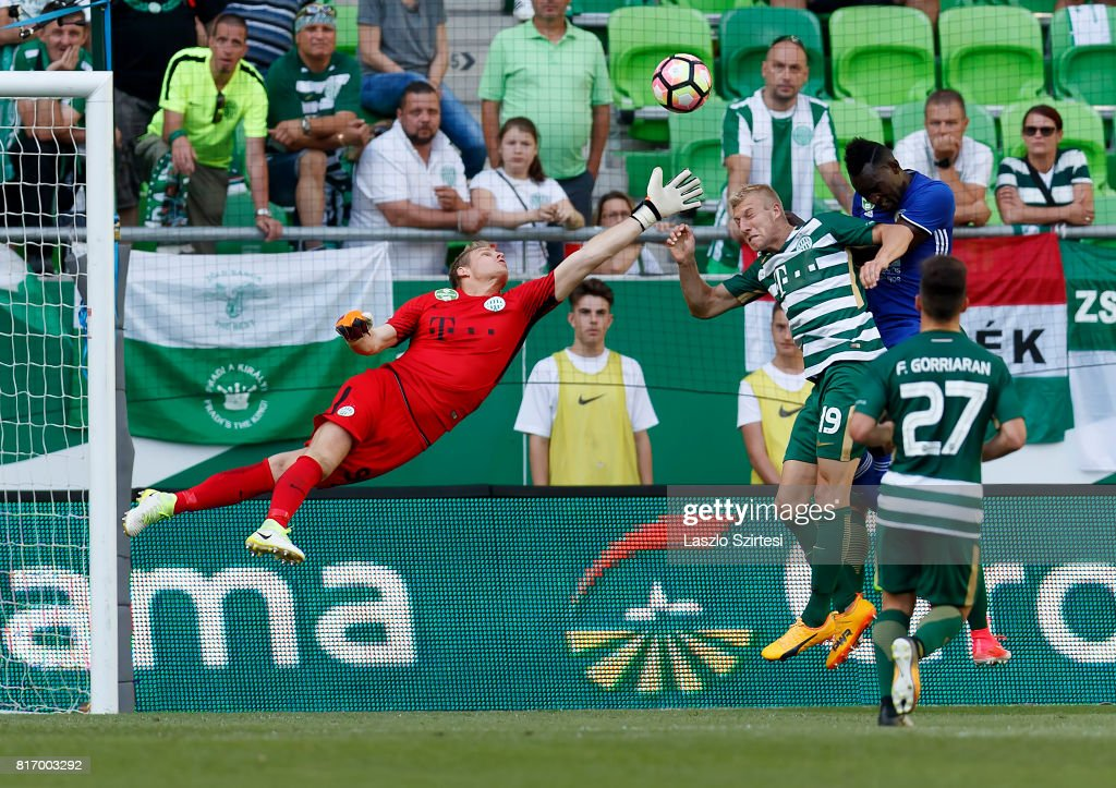 Goalkeeper Denes Dibusz (L) of Ferencvarosi TC reaches out his hand for the ball next to Julian Koch'' #19 of Ferencvarosi TC and Ulysse Diallo (R) of Puskas Akademia FC during the Hungarian OTP Bank Liga match between Ferencvarosi TC and Puskas Akademia FC at Groupama Arena on July 16, 2017 in Budapest, Hungary.