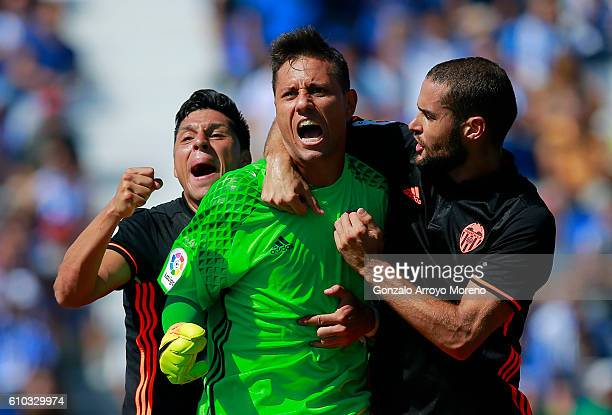 Goalkeeper Diego Alves of Valencia CF celebrates stopping a penalty shot with teammates Mario Suarez and Enzo Perez during the La Liga match between...