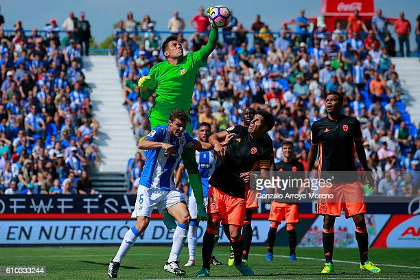 Goalkeeper Diego Alves of Valencia CF stops the ball ahead Alberto Martin of Deportivo Leganes during the La Liga match between CD Leganes and...