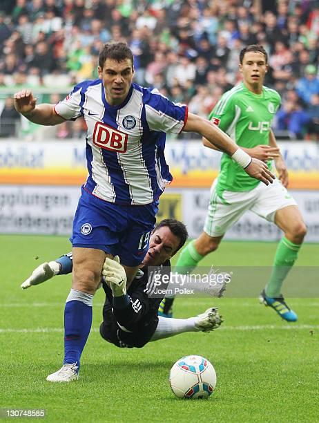 Goalkeeper Diego Benaglio of Wolfsburg fouls PierreMichel Lasogga of Berlin battle for the ball during the Bundesliga match between VfL Wolfsburg and...