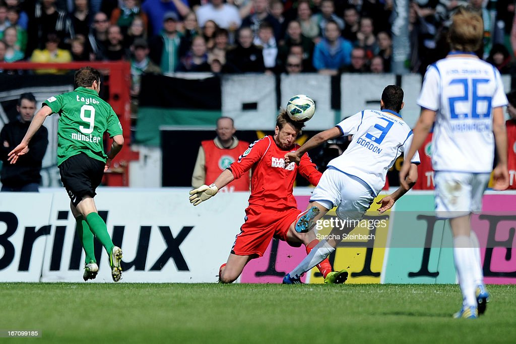 Goalkeeper Dirk Orlishausen (C) of Karlsruhe is beaten by Matthew Taylor (L) of Muenster scoring his 2nd goal during the 3. Liga match between Preussen Muenster and Karlsruher SC at Preussenstadion on April 20, 2013 in Muenster, Germany.