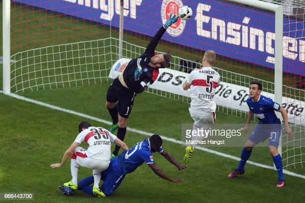 Goalkeeper Dirk Orlishausen of Karlsruhe makes a save ahead of Timo Baumgartl and Marcin Kaminski of Stuttgart during the Second Bundesliga match...
