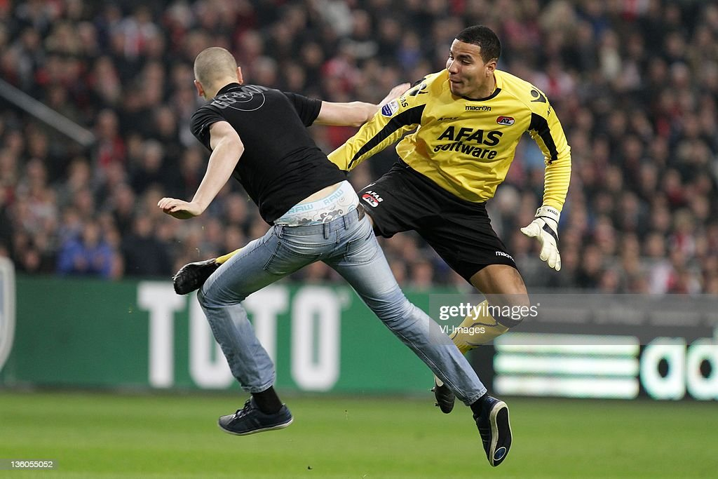 Goalkeeper Esteban Alvarado Brown of AZ Alkmaar retaliates as he is attacked by a supporter during the Dutch cup match between Ajax and AZ Alkmaar at...