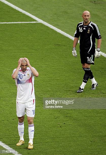 Goalkeeper Fabien Barthez of France looks on whilst a dejected Zinedine Zidane of France holds his head in his hands after Marco Materazzi of Italy...