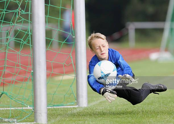 A goalkeeper from the 911 year old age group leaps save a shot on goal during the German Football Association's EYouth children's soccer tournament...