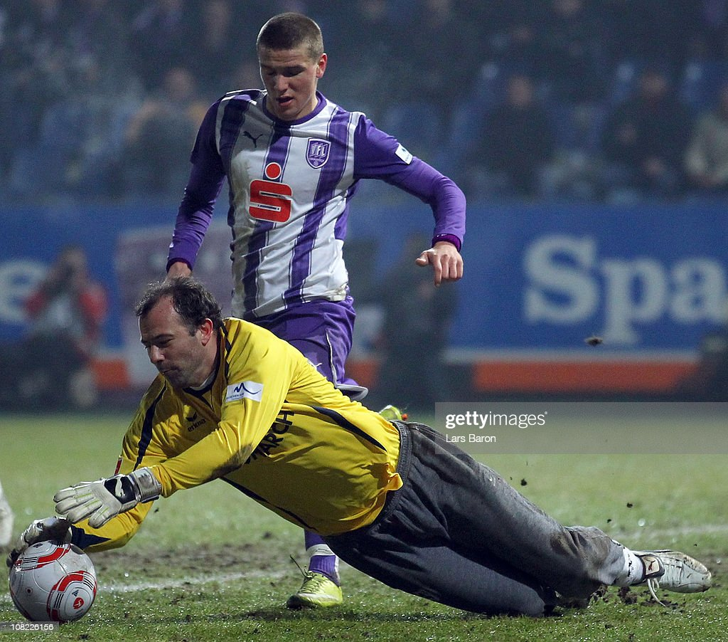 Goalkeeper Gabor Kiraly of Muenchen catches the ball infront of Flamur Kastrati of Osnabrueck during the Second Bundesliga match between VfL Osnabrueck and 1860 Muenchen at osnatel Arena on January 21, 2011 in Osnabruck, Germany.