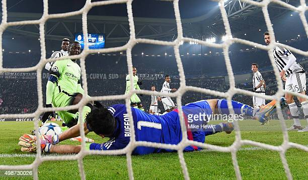 Goalkeeper Gianluigi Buffon of Juventus makes a save from Yaya Toure of Manchester City during the UEFA Champions League group D match between...