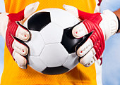 Goalkeeper holding football, mid section, close-up