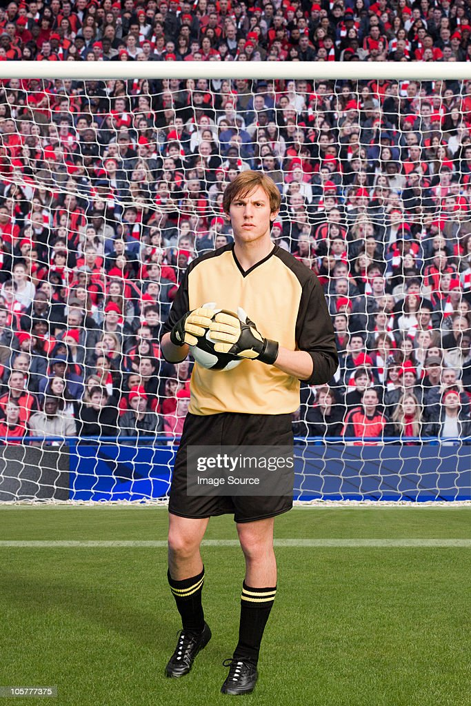 Goalkeeper holding football : Stock Photo