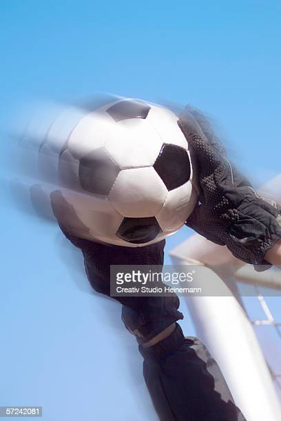 Goalkeeper holding soccer ball, low angle view