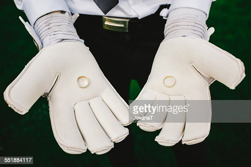 Goalkeeper holding wedding rings in gloves