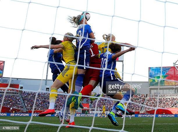 Goalkeeper Hope Solo of the United States jumps with a group to make a save in the first half against Sweden in the FIFA Women's World Cup Canada...