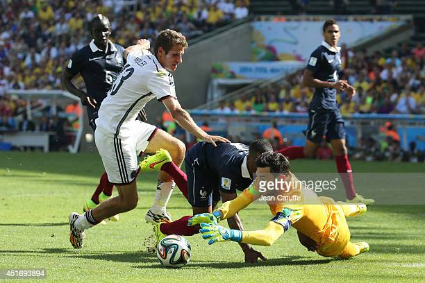 Goalkeeper Hugo Lloris of France catches the ball as Thomas Mueller of Germany and Patrice Evra of France look on during the 2014 FIFA World Cup...