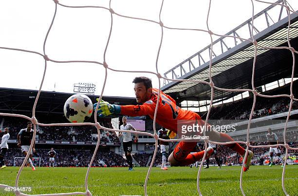Goalkeeper Hugo Lloris of Spurs dives in vain as Stewart Downing of West Ham scores his team's second goal during the Barclays Premier League match...