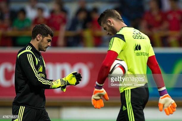 goalkeeper Iker Casillas of Spain crosses with his teammate goalkeeper David de Gea during their warming up prior to start the international friendly...