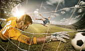 The soccer goalkeeper in gate jumping to catching ball. Collage. Advertising concept of soccer football