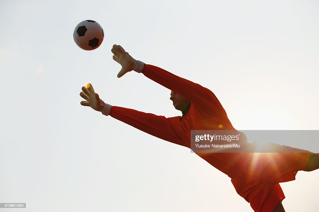Goalkeeper in orange uniform catching the ball