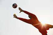 Goalkeeper in orange uniform catching the ball
