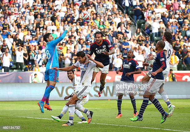 Goalkeeper Jaime Penedo of the Los Angeles Galaxy punches the ball away for a save Jermaine Jones of the New England Revolution goes over the top of...
