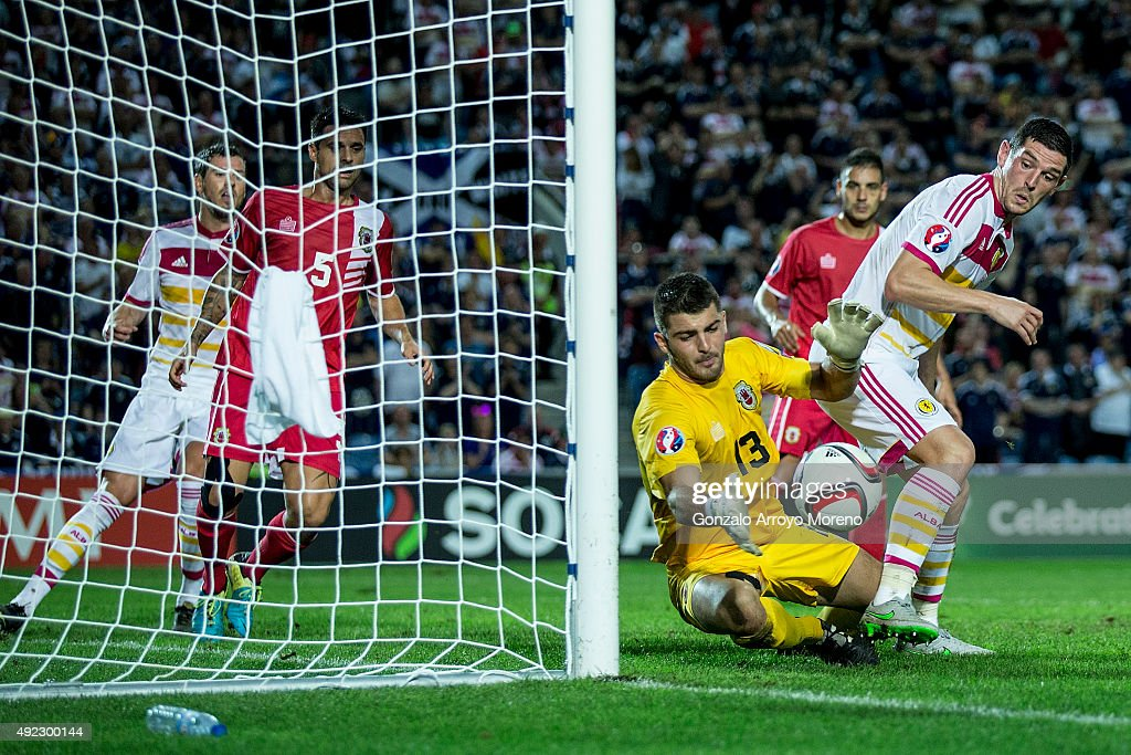 goalkeeper Jamie Robba (L) of Gibraltar stops the ball striked by Graham Dorrans (R) of Scotland during the UEFA EURO 2016 Qualifying round Group G match between Gibraltar and Scotland at Estadio Algarve on October 11, 2015 in Faro, Portugal.