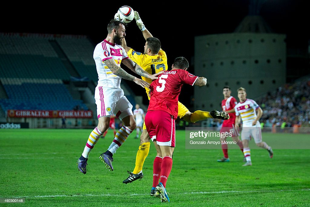 Goalkeeper Jamie Robba (2ndR) of Gibraltar stops the ball with his teammate Ryan Casciaro (R) against Steven Fletcher (L) of Scotland during the UEFA EURO 2016 Qualifying round Group G match between Gibraltar and Scotland at Estadio Algarve on October 11, 2015 in Faro, Portugal.